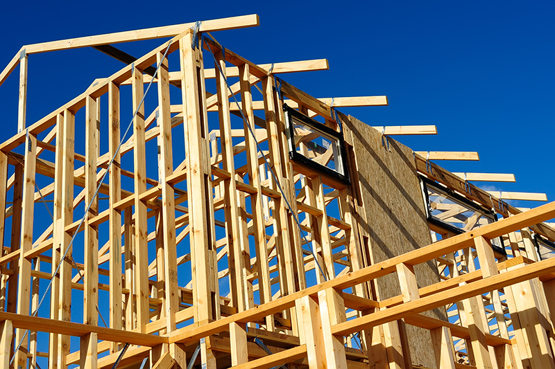 New residential construction house framing against a blue sky seen while preforming home inspection services
