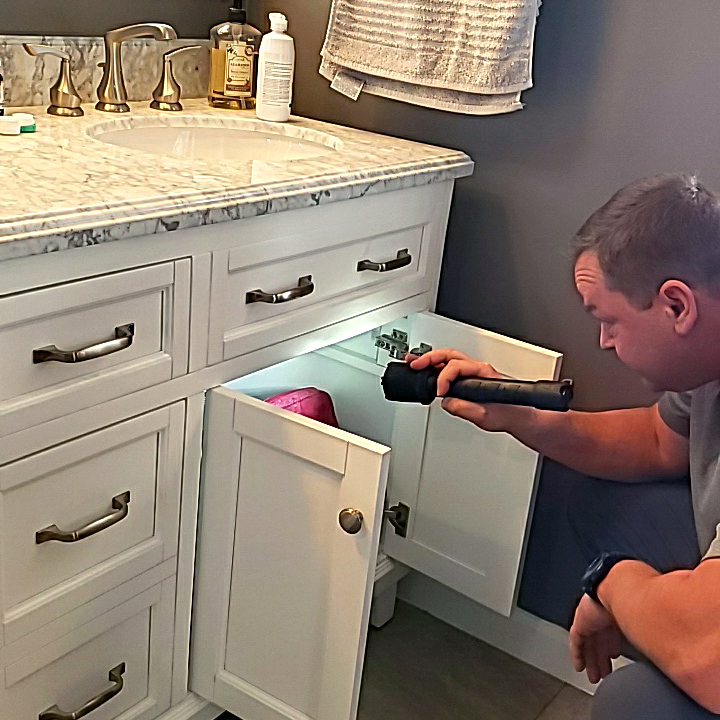 John, one of our home inspectors, inspecting under a bathroom sink