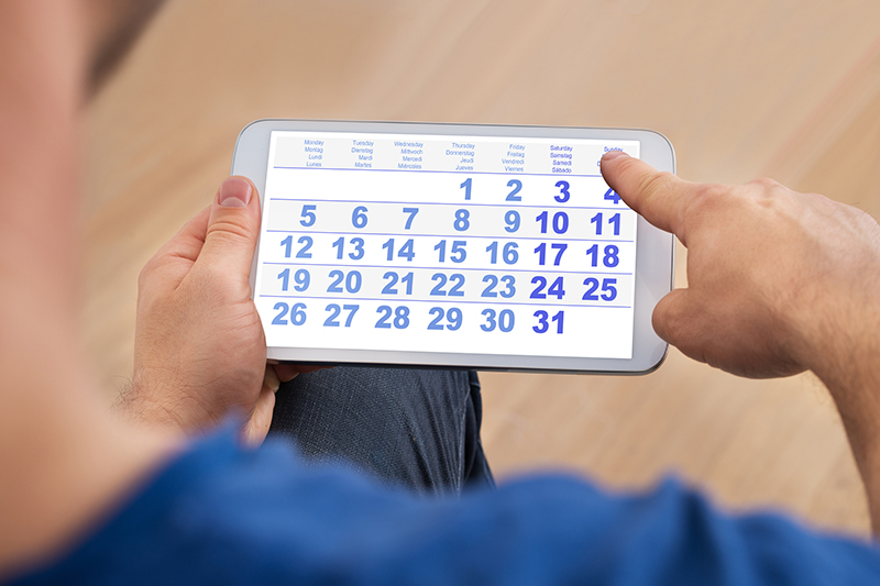 Close-up Of A Man Looking At Calendar On A Tablet Marking Time Passed Since Home Inspection Services were done.